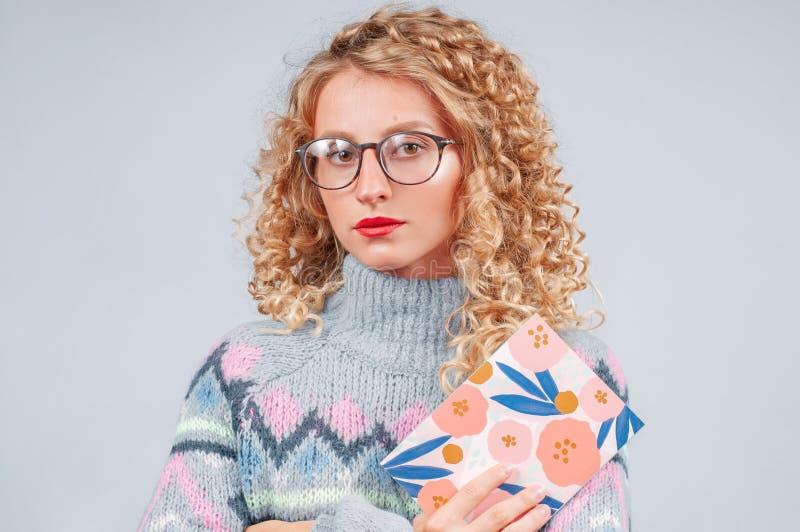 Jeune femme attirante avec les cheveux bouclés et les lunettes photographie stock libre de droits