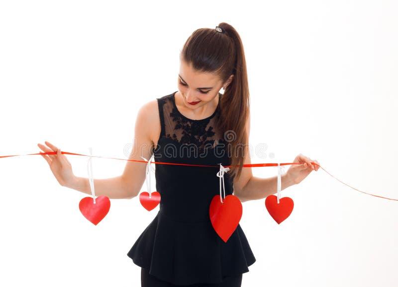 Jeune femme attirante avec les lèvres rouges célébrant le jour de valentines avec des coeurs d'isolement sur le fond blanc image stock