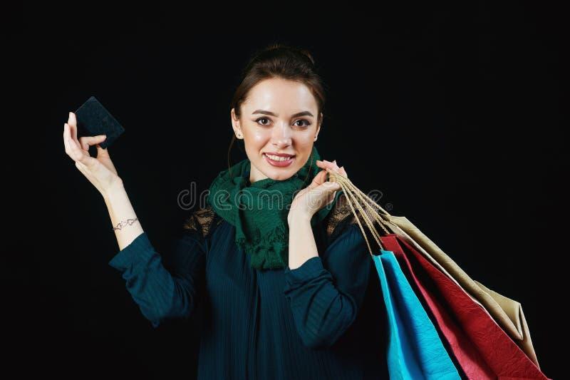 Jeune femme attirante avec les paniers et la carte de crédit photo stock