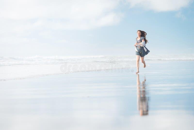 Jeune femme attirante courant à stupéfier la plage du Nouvelle-Zélande images libres de droits