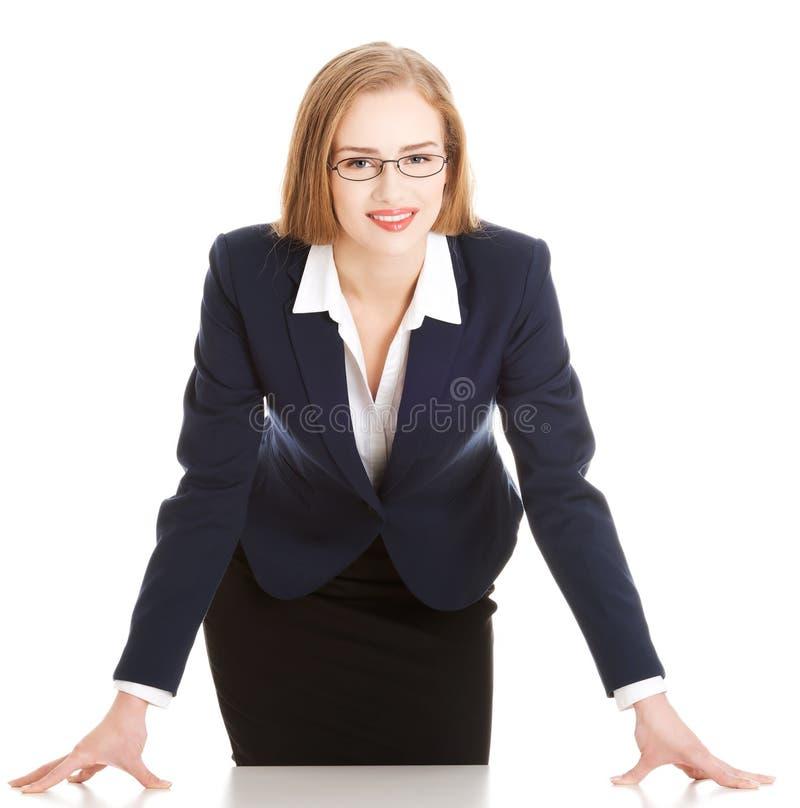 Jeune femme attirante d'affaires se pliant au-dessus de la table. photographie stock