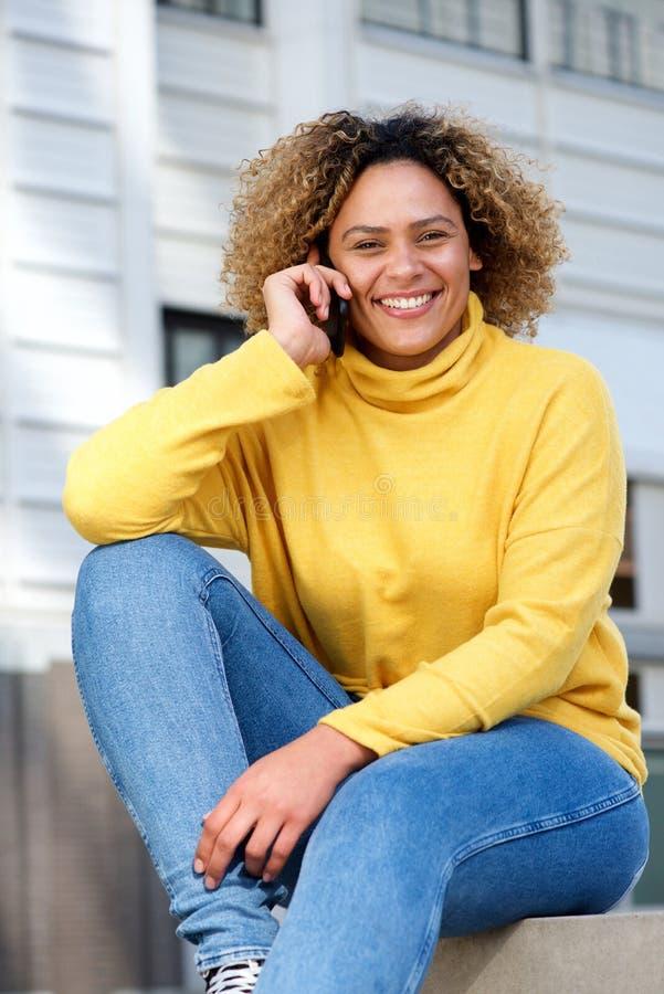 Jeune femme attirante d'afro-américain parlant au téléphone dans la ville images stock