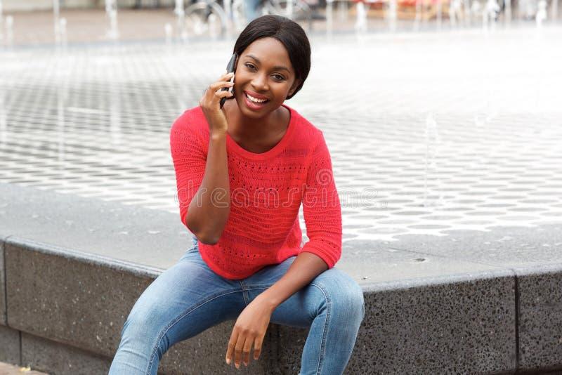 Jeune femme attirante d'afro-américain parlant au téléphone portable dans la ville photographie stock