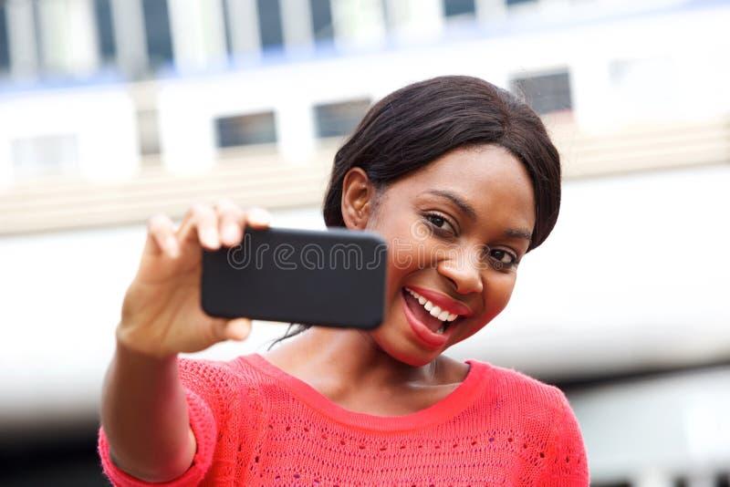 Jeune femme attirante d'afro-américain prenant le selfie dans la ville image libre de droits