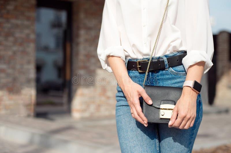 Jeune femme attirante dans des jeans et une position blanche de chemise sur la rue tenant le sac d'une dame dans ce qui se trouve photographie stock libre de droits