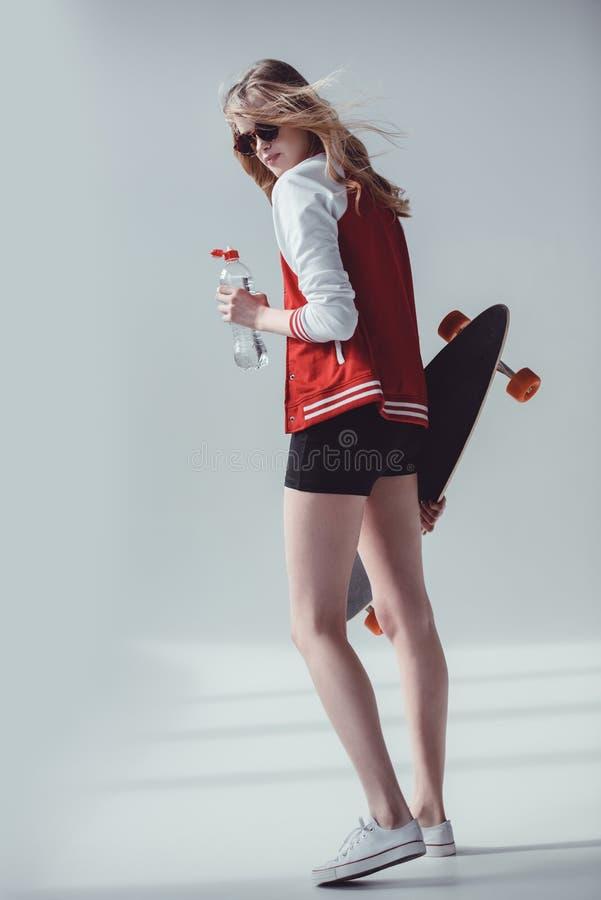 Jeune femme attirante dans des lunettes de soleil tenant la planche à roulettes et la bouteille avec de l'eau images stock
