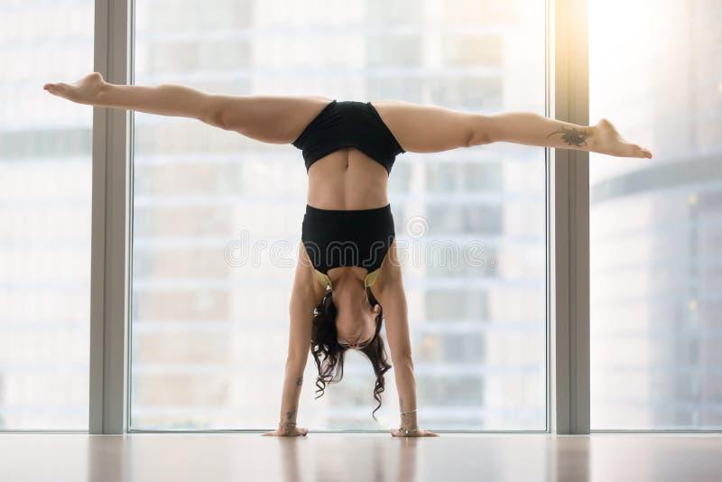 Jeune femme attirante dans la pose de danse contre la fenêtre de plancher, mains images stock