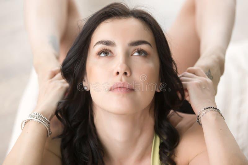 Jeune femme attirante dans la pose de Dhanurasana, plan rapproché de son visage images stock