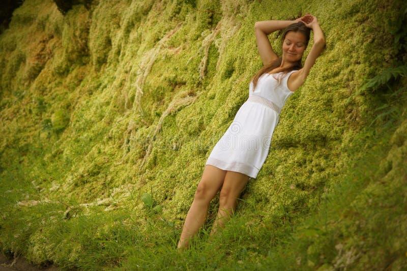Jeune femme attirante dans la robe blanche se tenant près du mur herbeux vert images libres de droits