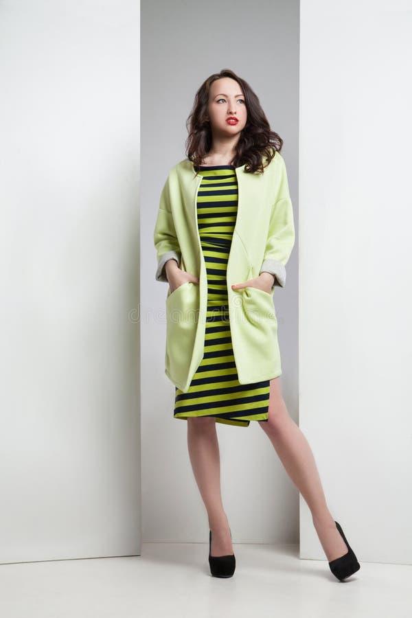 Jeune femme attirante dans la robe et le manteau rayés images stock