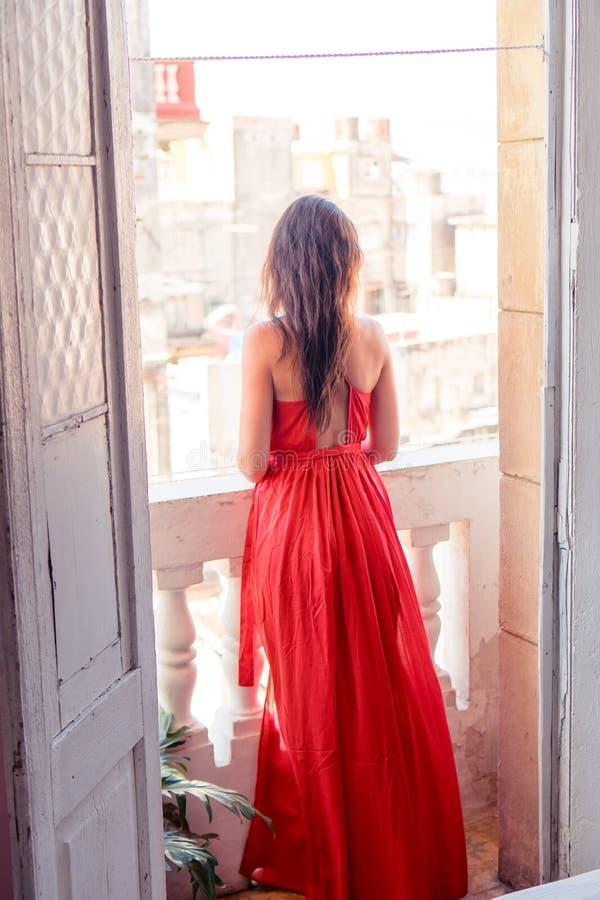 Jeune femme attirante dans la robe rouge sur le vieux balcon en appartement à La Havane photographie stock libre de droits