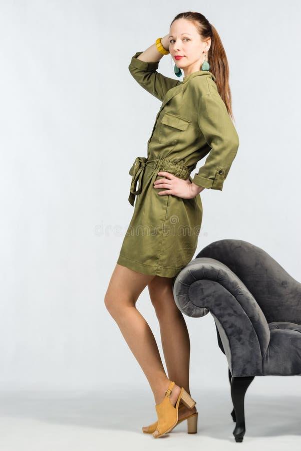 Jeune femme attirante dans la robe verte élégante posant par le sofa image libre de droits
