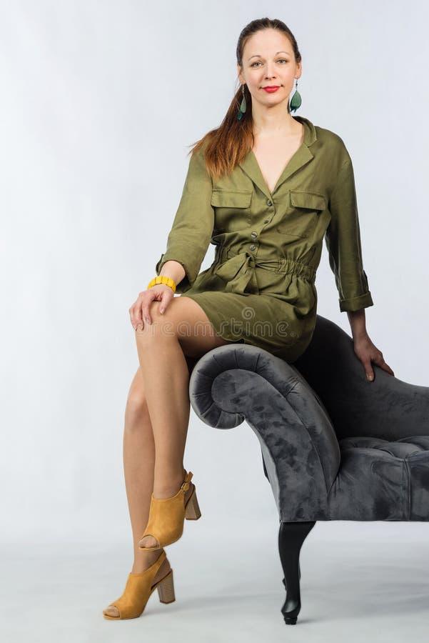 Jeune femme attirante dans la robe verte élégante posant par le sofa image stock