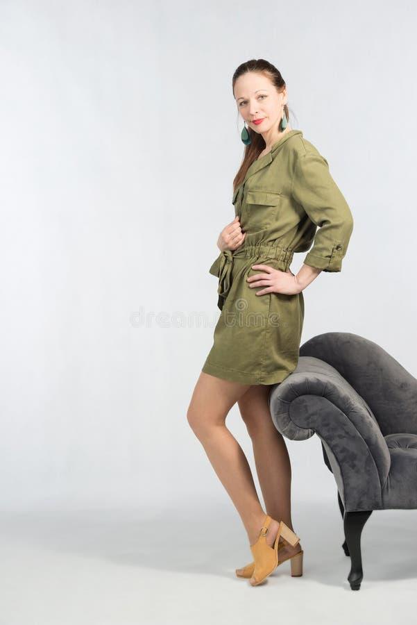 Jeune femme attirante dans la robe verte élégante posant par le sofa photos libres de droits