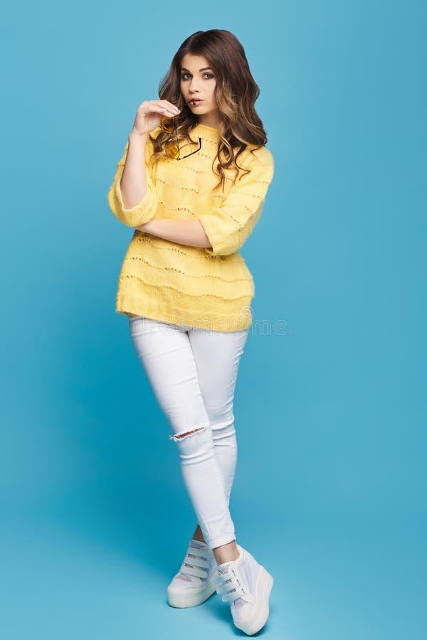 Jeune femme attirante dans le chandail jaune posant sur le fond bleu Jolie fille en verres jaunes photographie stock libre de droits