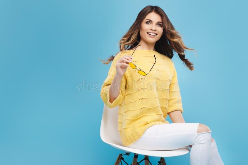 Jeune femme attirante dans le chandail jaune posant sur le fond bleu Jolie fille en verres jaunes image libre de droits