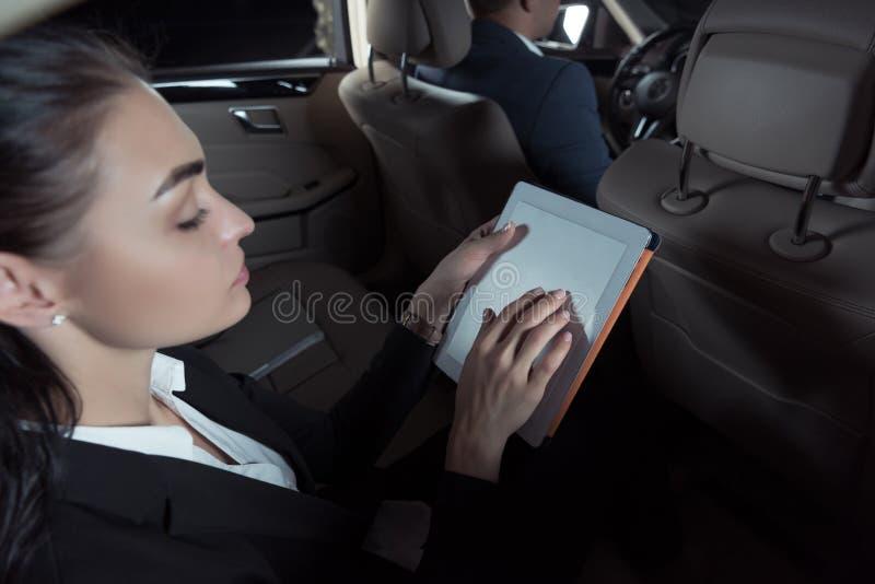 Jeune femme attirante dans le costume se reposant dans la banquette arrière de la voiture et de l'utilisation photographie stock