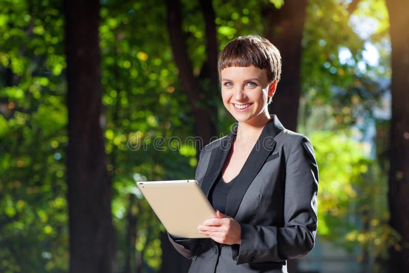 Jeune femme attirante dans le formalwear tenant le comprimé numérique photographie stock