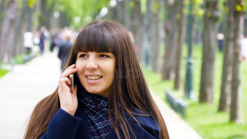 Jeune femme attirante dans le manteau bleu parlant au téléphone portable dans l'allée en parc Fille heureuse parlant dessus photos stock