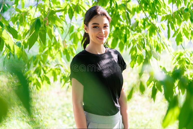 Jeune femme attirante dans le T-shirt vide noir dehors L'espace vide Copiez l'espace photos stock