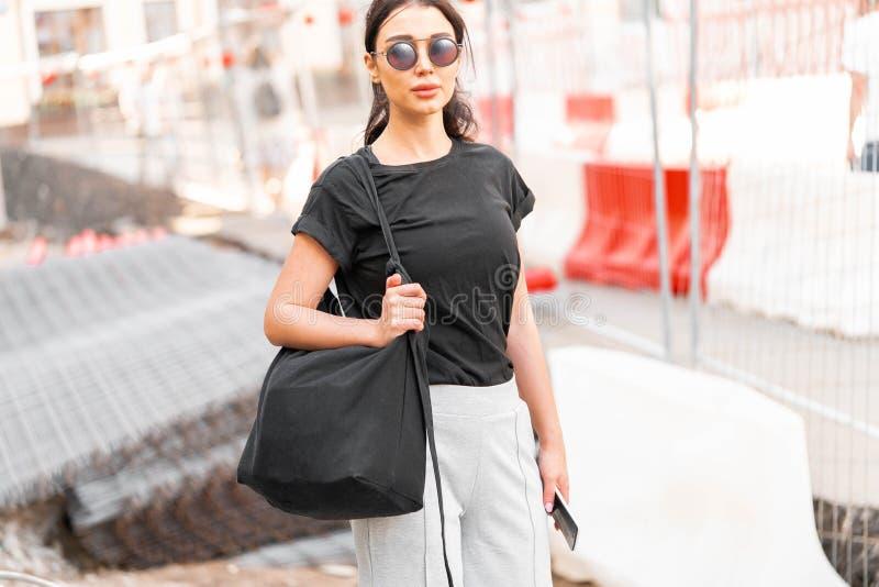 Jeune femme attirante dans le T-shirt vide noir dehors L'espace vide Copiez l'espace image libre de droits