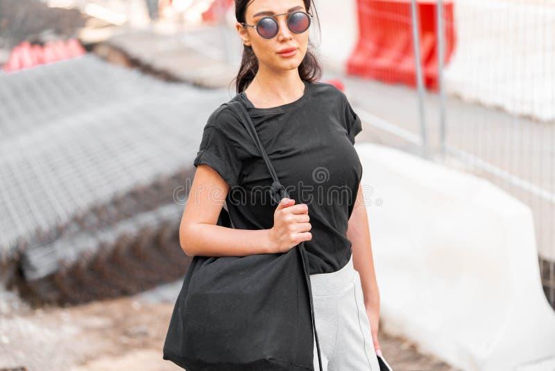 Jeune femme attirante dans le T-shirt vide noir dehors L'espace vide Copiez l'espace photographie stock