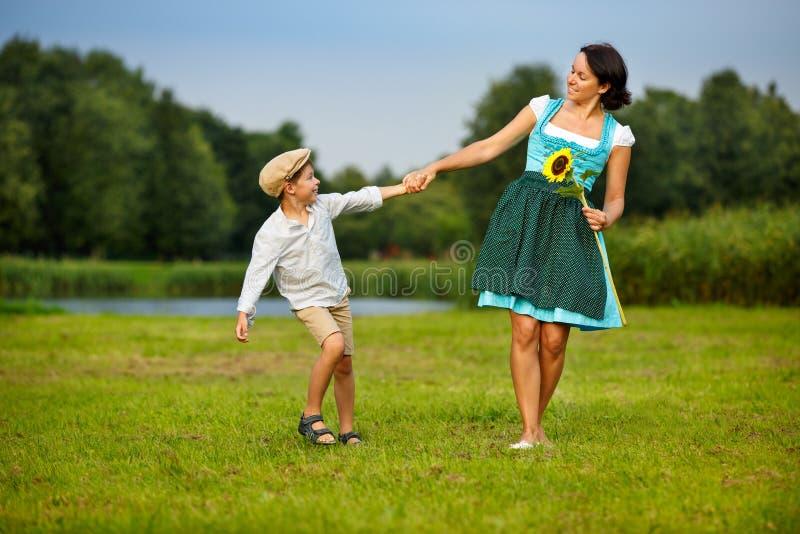 Jeune femme attirante dans un dirndl avec son fils photographie stock libre de droits