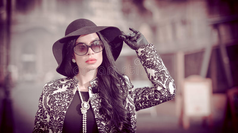 Jeune femme attirante dans un tir de mode de l'hiver Belle jeune fille à la mode dans la pose noire sur l'avenue Brune élégante photo stock
