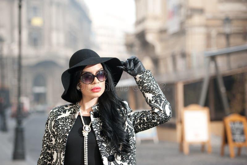 Jeune femme attirante dans un tir de mode de l'hiver Belle jeune fille à la mode dans la pose noire sur l'avenue Brune élégante photographie stock