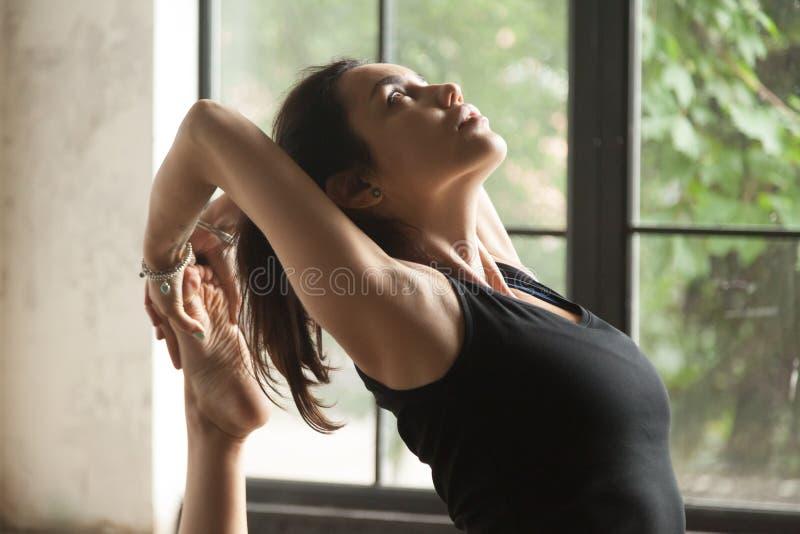 Jeune femme attirante dans une pose à jambes du Roi Pigeon, plan rapproché photos stock