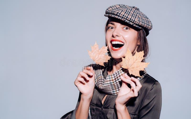 Jeune femme attirante dans vêtements saisonniers avec la feuille d'or Étonnez la femme jouant avec des feuilles et regardant l'ap image stock