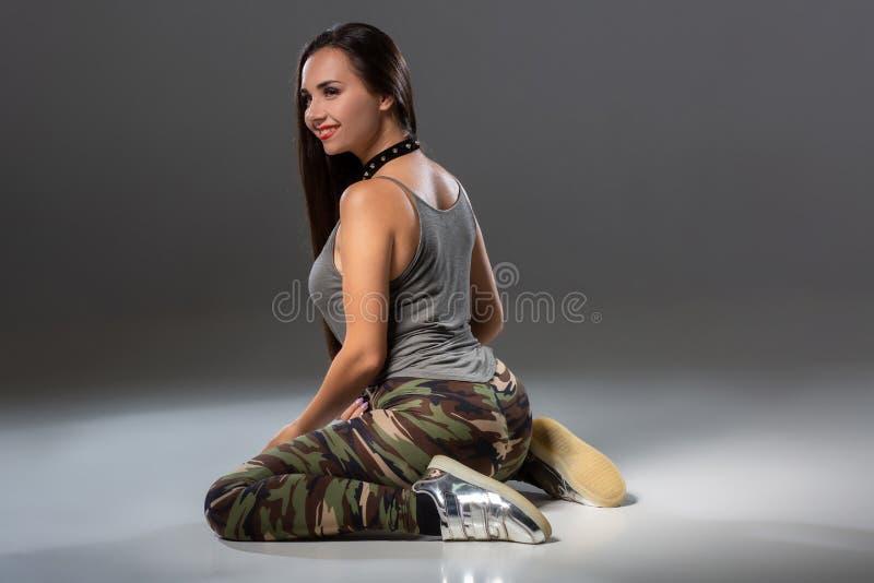 Jeune femme attirante de brune dans la danse de danse de butin de studio sur un fond foncé photo libre de droits