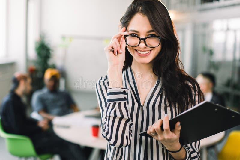 Jeune femme attirante de concepteur en verres souriant à la caméra dans le bureau créatif tandis que ses collègues s'asseyant au image stock