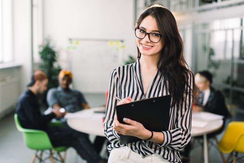 Jeune femme attirante de concepteur en verres souriant à la caméra dans le bureau créatif tandis que ses collègues s'asseyant au photographie stock