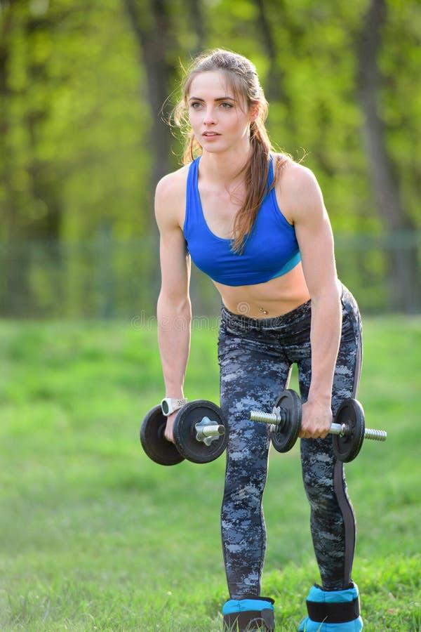 Jeune femme attirante de forme physique faisant l'exercice d'haltère sur extérieur photos stock