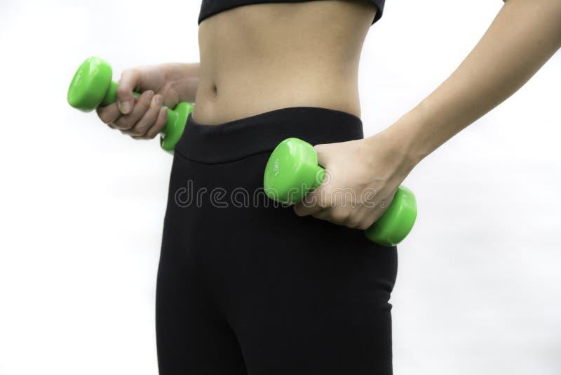 Jeune femme attirante de forme physique jugeant des haltères d'isolement sur le whi photo stock
