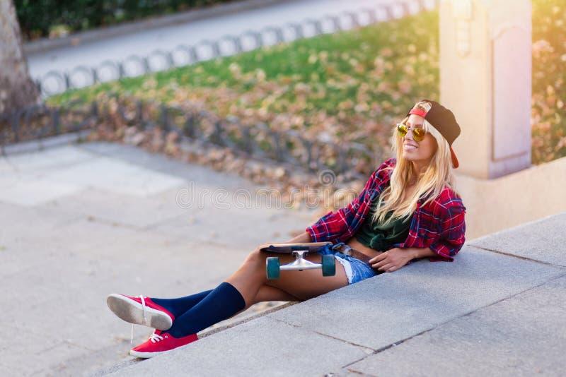 Jeune femme attirante de patineur prenant un bain de soleil dans la rue photographie stock