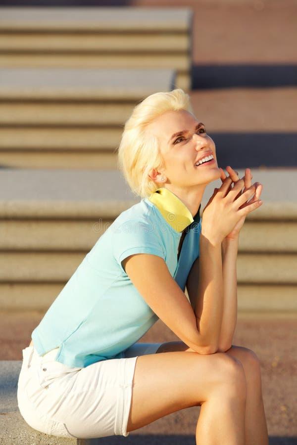 Jeune femme attirante de sourire s'asseyant dehors image libre de droits