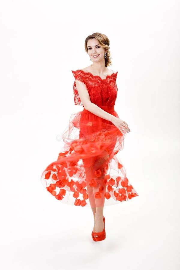 Jeune femme attirante en égalisant la robe rouge sur le fond blanc images libres de droits