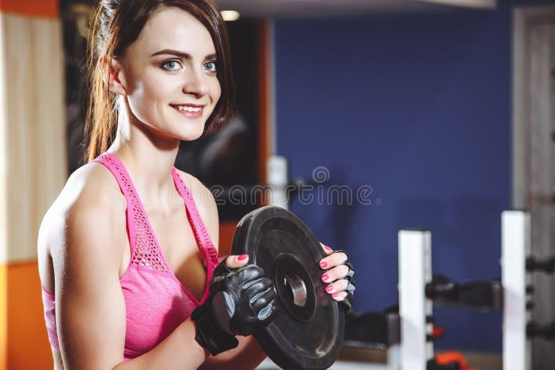 Jeune femme attirante faisant des exercices avec les plats lourds de barbell dans le gymnase Séance d'entraînement de Crossfit images stock
