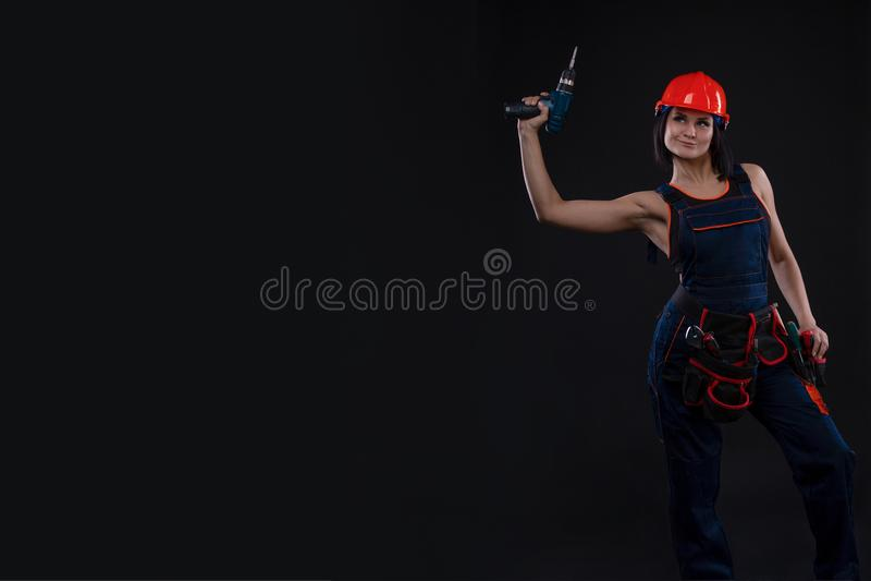 Jeune femme attirante faisant des réparations au fond noir Portrait d'un travailleur de la construction féminin Bâtiment, concept photo libre de droits