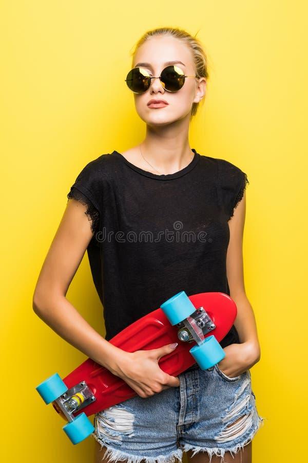 Jeune femme attirante heureuse dans des lunettes de soleil se reposant sur la planche à roulettes au-dessus du fond jaune photos stock