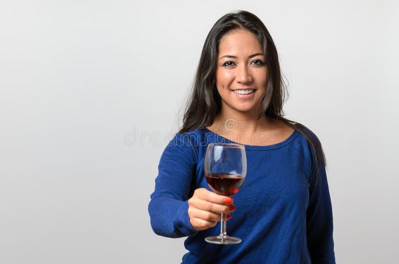 Jeune femme attirante heureuse grillant avec du vin image stock