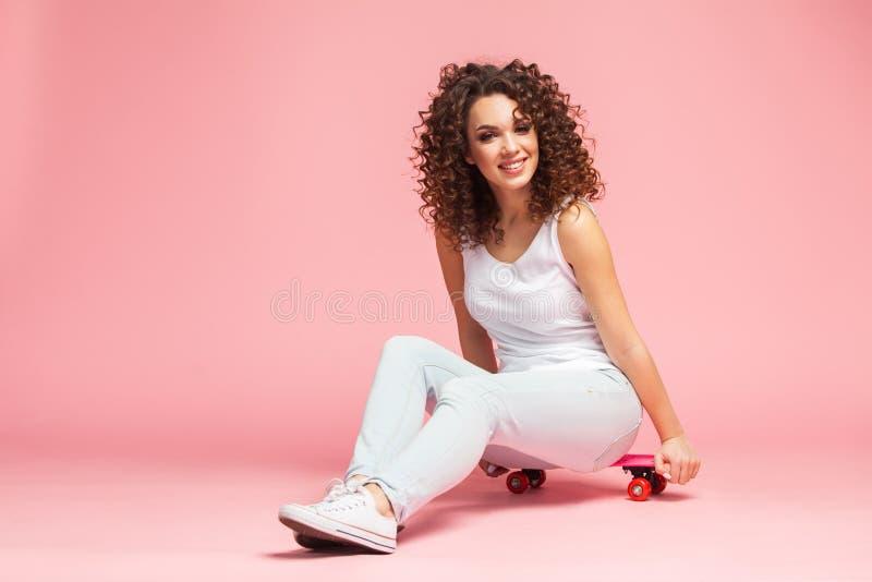 Jeune femme attirante heureuse s'asseyant sur la planche à roulettes au-dessus du fond rose photographie stock