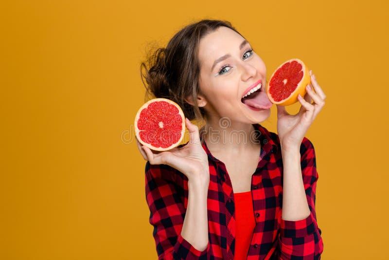 Jeune femme attirante heureuse tenant et léchant la moitié du pamplemousse photographie stock