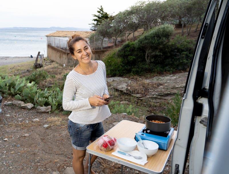 Jeune femme attirante hippie heureuse faisant cuire en dehors de elle campervan près de la plage photo stock
