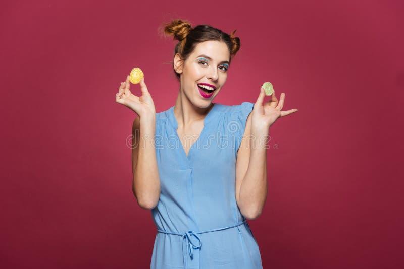 Jeune femme attirante joyeuse tenant et tenant des sucreries de confiture d'oranges photographie stock libre de droits
