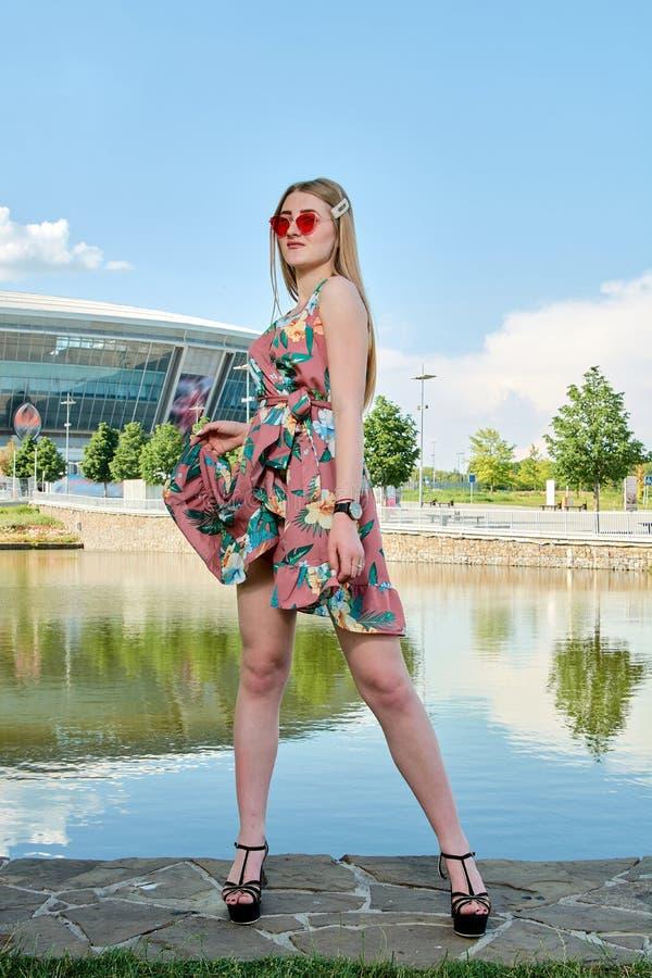 Jeune femme attirante Lunettes de soleil rouges, robe de couleur Portrait du ` s de fille Fond de stade de football image libre de droits