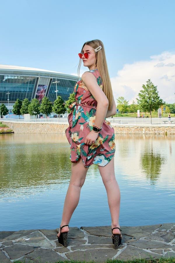 Jeune femme attirante Lunettes de soleil rouges, robe de couleur Portrait du ` s de fille Fond de stade de football photos libres de droits