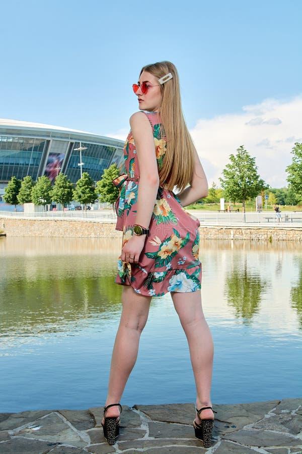 Jeune femme attirante Lunettes de soleil rouges, robe de couleur Portrait du ` s de fille Fond de stade de football images libres de droits